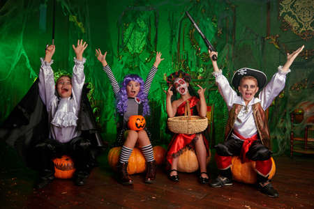 Halloween. Funny kids in carnival costumes are sitting with pumpkins the old castle on Halloween.