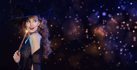 Portrait of a beautiful young witch in a hat and with a magic wand smiles, surrounded by magic lights. Halloween celebration, party. Copy space. Stock Photo