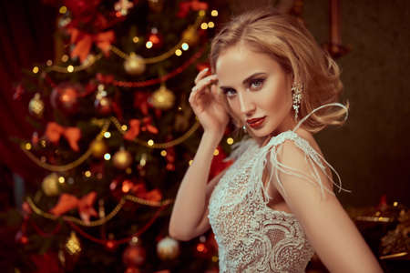 Christmas and New Year concept. Fashionable young woman wearing luxurious evening dress and with beautiful evening makeup and hairstyle in the fairy beautiful Christmas interior. Christmas tree in the background. Jewelery. Imagens