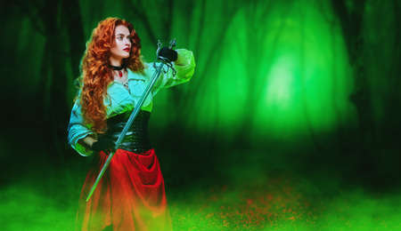 Portrait of a beautiful red-haired girl with a battle epee (rapier) standing in a magic forest. The heroine of an adventure novel. Copy space.