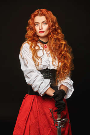 Portrait of a beautiful red-haired girl with a battle epee (rapier) on a black background. Historical reconstruction of the 16-17th centuries. 写真素材
