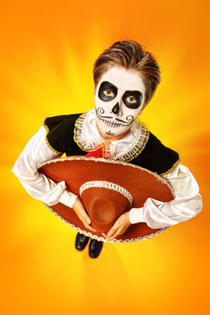 Portrait of a handsome boy with sugar skull makeup holding sombrero in his hands over bright yellow background. Halloween. Dia de los muertos. Day of the dead. Copy space. 写真素材