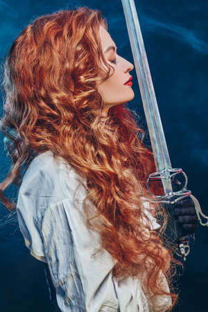 Profile portrait of a beautiful and brave red-haired woman with a battle epee (rapier). Historical reconstruction of the 16-17th centuries. 写真素材