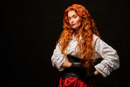 Portrait of a beautiful young woman with magnificent red hair in a historical costume of 16-17th centuries smiling at camera. Studio portrait on a black background. Copy space.