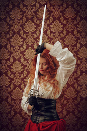 Beautiful and brave red-haired woman with a battle epee (rapier) on a vintage background. The heroine of a historical adventure novel.