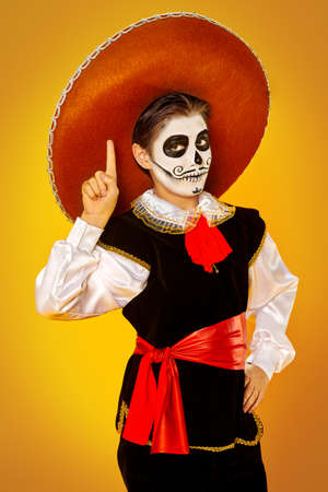 Portrait of a handsome boy with sugar skull makeup over bright yellow background. Halloween. Dia de los muertos. Day of the dead. Copy space. 写真素材