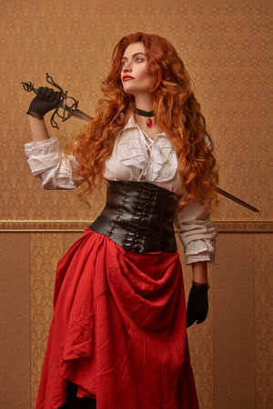 Historical reconstruction of the 16-17th centuries. Portrait of a beautiful red-haired woman with a battle epee (rapier) on a vintage background. 写真素材