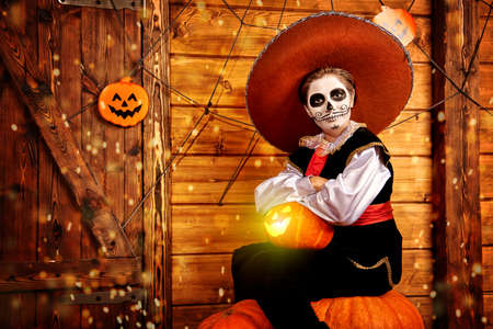Handsome boy with sugar skull makeup posing with pumpkins in a wooden house decoration. Halloween party. Dia de los muertos. Day of the dead.