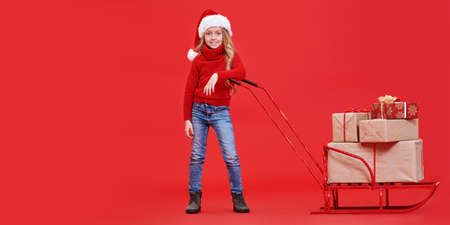 Merry Christmas and Happy New Year! Cute little girl in Christmas hat posing next to the sled with gifts. Studio portrait over festive red background. 写真素材