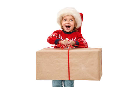 Merry Christmas and Happy New Year! Cute emotional little boy in Santa Claus hat holds huge gift box and and shouts with joy. Studio portrait over white background.