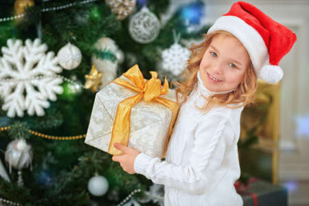 Merry Christmas and Happy New Year! Happy little girl in Santa Claus hat holds a box with gifts and smiles. Beautiful Christmas tree in the background.
