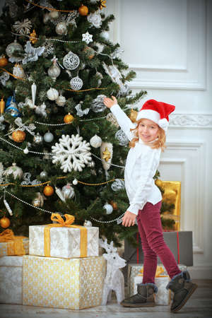 Merry Christmas and Happy New Year! Happy little girl in Santa Claus hat decorates the Christmas tree with toys. Beautiful Christmas tree in the background.