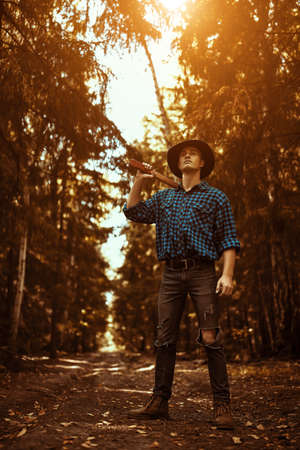 Full length portrait of a handsome strong man lumberjack with an ax in the wild forest.