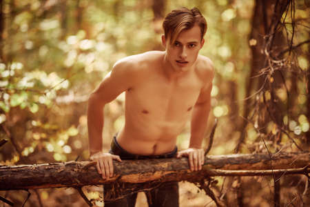 Handsome athletic young man in the wild forest. Outdoor activities and sports.