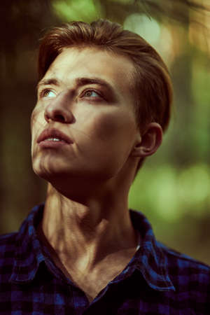Handsome young man standing in the shadow of the forest and the rays of the sun fall on his face. Male beauty.