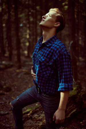 Handsome masculine man in the wild forest. Adventure, spirit of freedom. Active lifestyle.