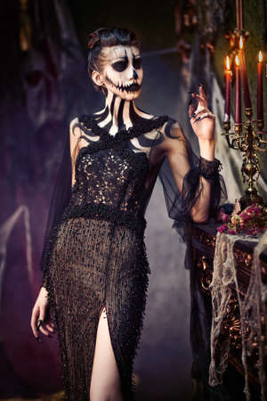 Beautiful elegant lady with skull pumpkin makeup in the old castle decorations. Vintage style. Halloween. Day of The Dead.