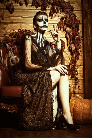 Beautiful elegant lady with skull pumpkin makeup sits in vintage armchair in autumn decorations. Halloween. Day of The Dead.