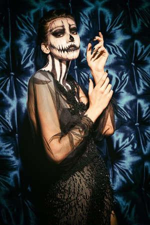 Beautiful and terrible pumpkin queen. Fashion model with skull pumpkin makeup. Halloween concept.