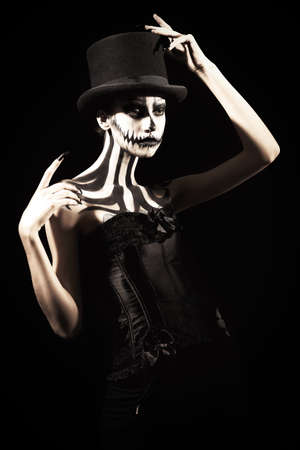 Elegant young woman in a male top-hat with pumpkin skull make-up over black background. Pumpkin queen. Costumes and makeup for Halloween.