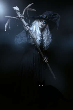 Halloween. Full length portrait of an ugly old witch standing with her magic staff on a black backgroung. Mysterious fog around. Witchcraft.