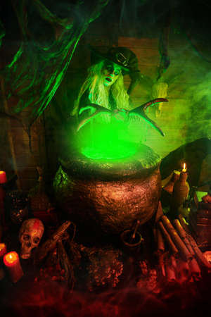 Horrible old witch holding staff above the boiling potion in a cauldron surrounded by a magical green light. Halloween. Witchcraft.