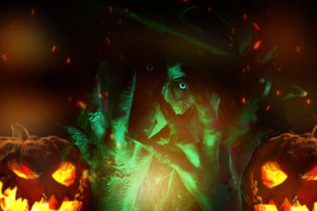 Close up portrait of scary ugly witch in green light with fire and sparks. Halloween. Scary tales. Stockfoto