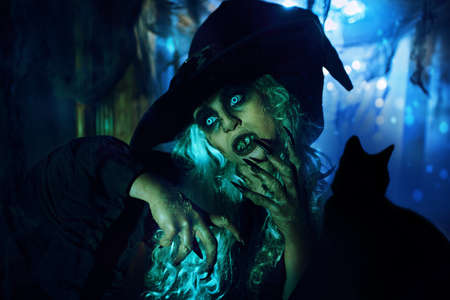 A scary ugly witch stands in an abandoned witch's den. Halloween. Scary tales. 写真素材