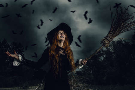 A portrait of an angry witch with a broomstick near the forest. Magic, dark force, spell.