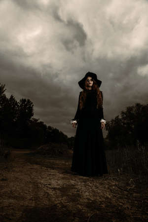 A portrait of a lonely dark witch near the forest. Magic, dark force, spell.