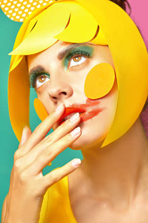 Bright style. Close up portrait of a fashionable beauty girl with colorful paper makeup and hairstyle and and smudged lipstick on green and fuchsia background. Party style. Makeup and cosmetics.