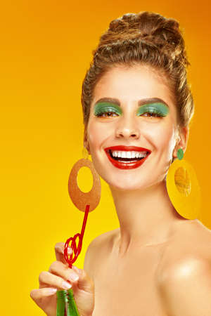 Beauty and pin-up style. Portrait of a cheerful young woman with colorful makeup and beautiful smile drinking soda on a yellow background. Makeup and cosmetics. Studio shot.