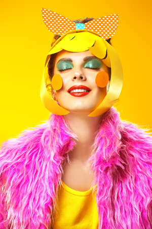 Fashion shot. Portrait of an attractive girl with colorful paper makeup and hairstyle posing in fashionable vivid clothes on a yellow background. Party style.