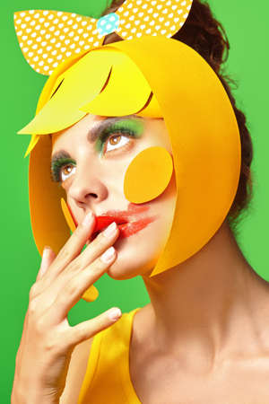 Bright style. Close up portrait of a fashionable beauty girl with colorful paper makeup and hairstyle and and smudged lipstick on green background. Party style. Makeup and cosmetics.
