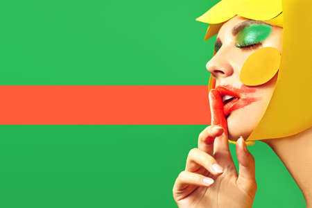Bright style. Close up portrait of a fashionable beauty girl with colorful paper makeup and hairstyle and and smudged lipstick on green background with red line. Party style. Makeup and cosmetics.