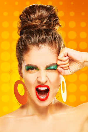 Beauty concept. Portrait of a screaming young woman with colorful makeup posing on a vivid yellow background. Makeup and cosmetics. Studio shot. Close up, 写真素材