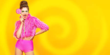Stunning fashionable model posing in pink clothes with lollipop on yellow background. Active bright lifestyle. Copy space. 写真素材
