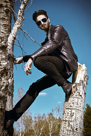Handsome young man in a black leather jacket and sunglasses sitting in a tree in open air. The spirit of freedom and adventure. Men's fashion.