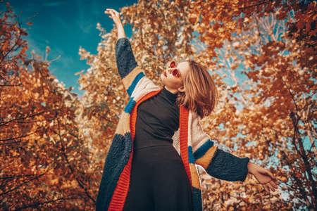 Beautiful modern girl is posing in motion in the autumn park. Seasonal style, autumn beauty, fashion.