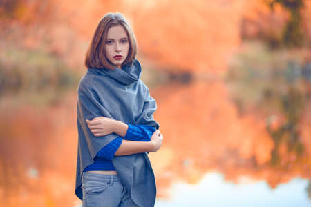 Autumn mood. Beautiful pensive girl stands on the shore of the pond in the autumn park. Beauty, fashion.
