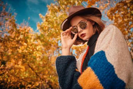 Beautiful modern girl in the autumn park. Seasonal style, autumn beauty, fashion.