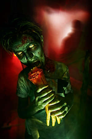 Halloween, horror movie. Portrait of a scary zombie boy teenager with a bloody hand torn off in smoke green and red light.