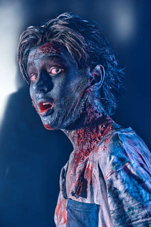 Portrait of a scary Halloween zombie boy teenager with bloody eyes. Halloween concept. Horror movie. 写真素材