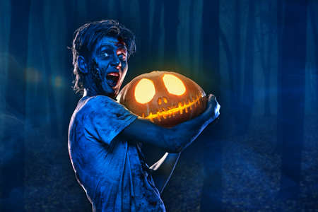 Halloween concept. Portrait of a scary zombie boy teenager holding a pumpkin lantern in forest. Copy space. 写真素材