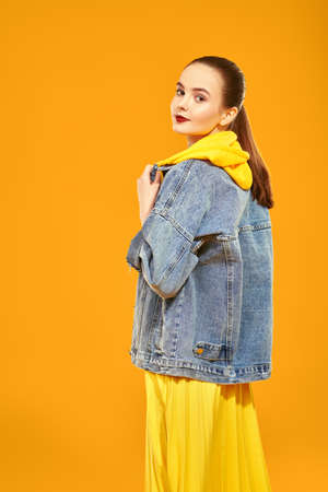 Modern youth look. Beautiful young girl in bright summer clothes posing on a yellow background. Beauty, fashion. 写真素材