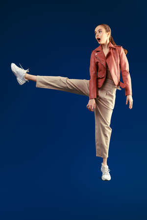 Portrait of an excited modern girl model in pants and leather jacket taking a wide step and opening her mouth in surprise on a dark blue background. Beauty, fashion. Copy space.