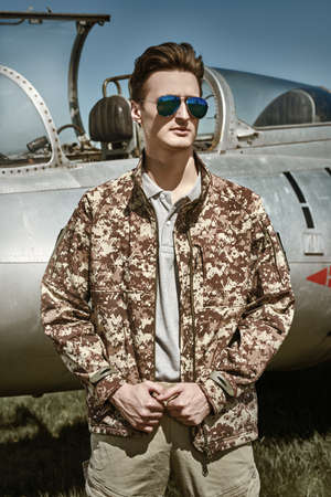 Handsome man pilot wearing military uniform stands by his fighter jet at the airfield. Military aircraft. Reklamní fotografie