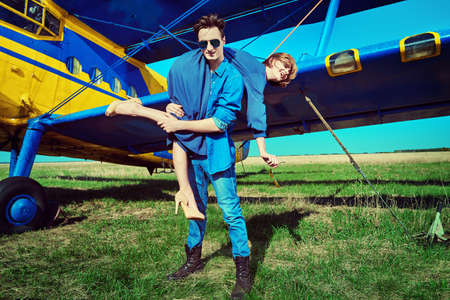Full length portrait of a beautiful passionate playful couple in love at the airport next to the plane. Adventure and travel concept. Reklamní fotografie