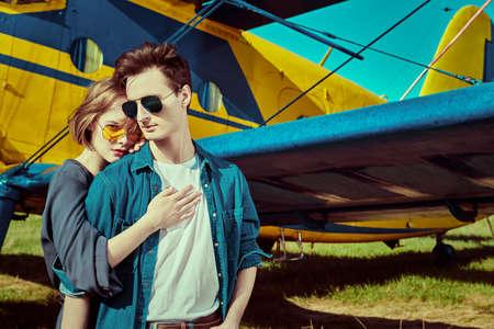Handsome man hugs his beautiful girlfriend before the flight. Aviation and love. Reklamní fotografie