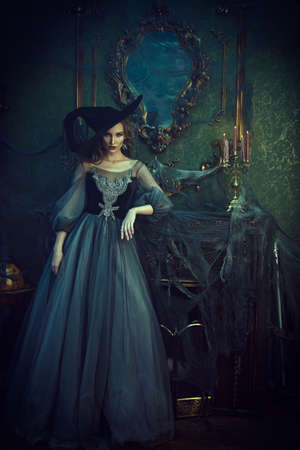 Magic Halloween. Beautiful young woman in a witch costume stands by the fireplace in the old castle. Celebration. Halloween party.